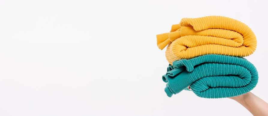 složeni džemperi u ruci