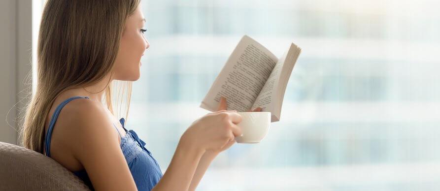 Devojka čita i pije kafu