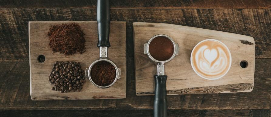 Vizual ručki za espreso aparat na drvenoj podlozi i zrna kafe pored